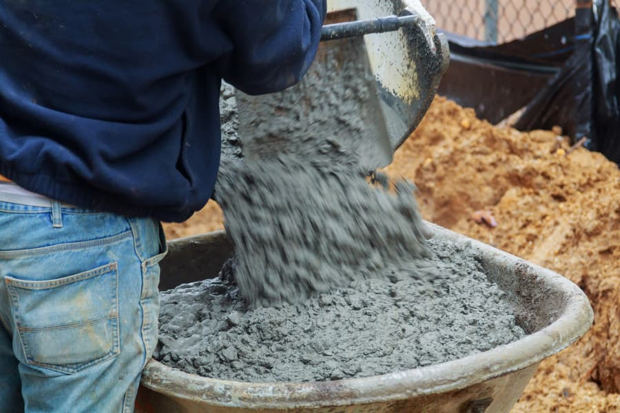 man directing concrete being poured into a wheelbarrow